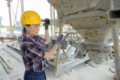 在混凝土搅拌机的女工混合的成份 免版税库存照片