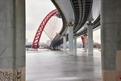 在混凝土桩之间的底视图在有红色曲拱的路桥梁 免版税库存照片
