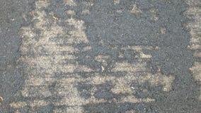 在混凝土的破旧的柏油碎石地面 库存照片