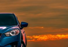 在混凝土路有体育和现代设计的停放的蓝色紧凑SUV汽车正面图在与美丽的橙色天空的日落 免版税库存图片