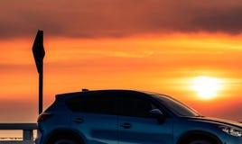 在混凝土路有体育和现代设计的停放的蓝色SUV汽车侧视图在日落 r 免版税库存图片