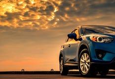 在混凝土路有体育和现代设计的蓝色紧凑SUV汽车停放的由有美丽的日落天空的海 ?? 库存图片