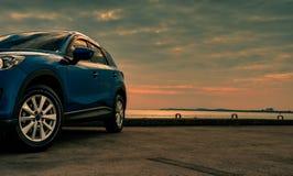 在混凝土路有体育和现代设计的蓝色紧凑SUV汽车停放的由海在日落在晚上 杂种和电 库存照片