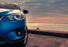 在混凝土路有体育和现代设计的蓝色紧凑SUV汽车停放的由海在日落在晚上 杂种和电 免版税库存照片