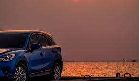 在混凝土路有体育和现代设计的蓝色紧凑SUV汽车停放的由海在日落在晚上 杂种和电 图库摄影