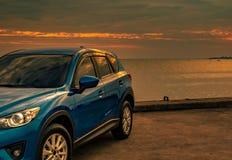 在混凝土路有体育和现代设计的蓝色紧凑SUV汽车停放的由海在日落在晚上 杂种和电 免版税库存图片