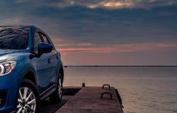 在混凝土路有体育和现代设计的蓝色紧凑SUV汽车停放的由海在日落在晚上 杂种和电 免版税图库摄影