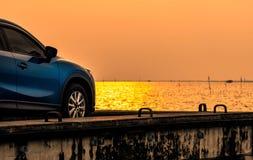 在混凝土路有体育和现代设计的蓝色紧凑SUV汽车停放的由海在日落 i 库存照片