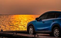 在混凝土路有体育和现代设计的蓝色紧凑SUV汽车停放的由海在日落 i 图库摄影