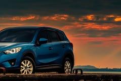 在混凝土路有体育和现代设计的蓝色紧凑SUV汽车停放的由海滩在日落 r 库存图片