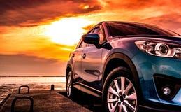 在混凝土路有体育和现代设计的蓝色SUV汽车停放的在日落与橙色天空的海海滩 杂种和电车 库存照片