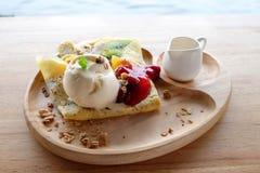 在混杂的果子绉纱的熔化的香草冰淇淋有在木板材的蜂蜜罐的 免版税库存图片
