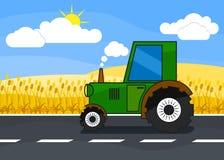 在清扫的路的拖拉机乘驾在麦子收获 免版税库存照片