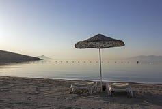 在清早海滩的两sunloungers 库存照片