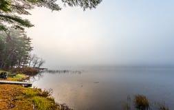 在清早雾的空的营火在渥太华,安大略附近的一个湖 库存图片