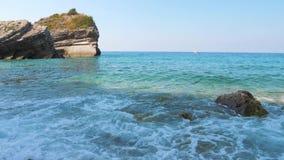 在清楚的天蓝色的海的岸的波浪有岩石的 股票录像