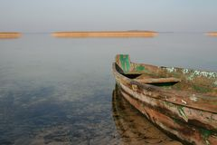 在清楚的水的老木小船 图库摄影