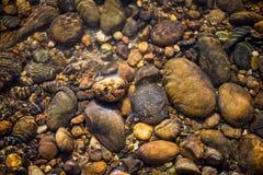 在清楚的河水下的自然颜色石头 库存图片