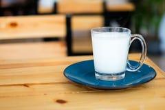 在清楚的玻璃的自创热的新鲜的牛奶与蓝色茶碟 免版税图库摄影