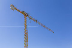 在清楚的蓝天的高起重机与一个通过的航空器 免版税图库摄影