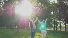 在清洁的一对浪漫夫妇在阳光的绿色树中 他们捉住飞行蒲公英 夏天 愉快 股票录像
