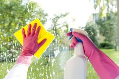 在清洗窗口的桃红色手套的女性手 库存照片