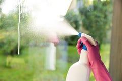 在清洗窗口的桃红色手套的女性手 免版税库存图片