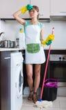在清洁期间疲倦的妇女在厨房 免版税库存图片