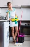 在清洁期间疲倦的妇女在厨房 免版税图库摄影