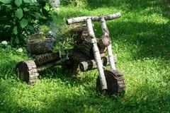 在清洁的森林里站立从木日志的一辆摩托车 库存照片