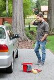 在清洗肮脏的汽车前的人 库存图片