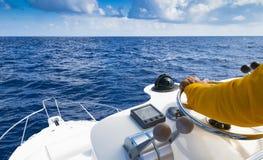 在渔场天期间,上尉的手汽船方向盘的在蓝色海洋 成功渔概念 海洋游艇 图库摄影
