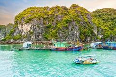 在渔夫和鱼或牡蛎农夫浮动村庄的小船在下龙湾,越南 免版税库存照片