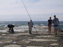 在渔夫旁边的家庭海滩的 免版税库存照片