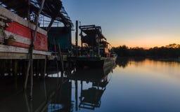 在渔夫村庄和木小船的镇静蓝色小时日落与 免版税库存照片