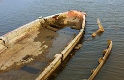 在渔夫的损坏的老小船供以人员海滩 库存图片