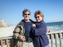 在渔码头的愉快的退休的夫妇在晴朗的海滩 免版税库存照片