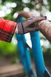 在渔网手套的女骑士手在老栏杆说谎 免版税库存图片
