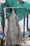 在渔船的大捕鱼网在码头 免版税库存照片