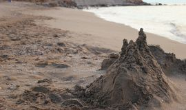 在温暖的南部的海的岸的沙子城堡手段 免版税库存照片