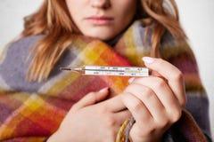 在温暖的床罩包裹的年轻女性播种的射击,显示高温的举行termometer,有流感,在白色 库存图片