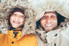 在温暖的戴头巾偶然附头巾皮外衣夹克外衣和儿子打扮的父亲走在多雪的森林快乐的笑容画象 库存图片