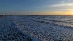 在温暖的日出的令人惊讶的4k空中寄生虫凸轮视图在佛罗里达可可粉的镇静白色泡沫海浪冲浪海滩海景 影视素材