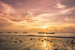 在温暖的日落的小船在海洋海岸 免版税库存照片