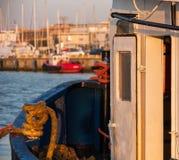 在温暖的日落的渔船在海 舱门和线的细节 免版税库存图片