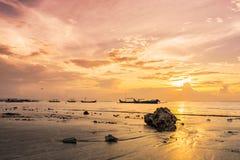 在温暖的日落的石头在海洋海岸 免版税库存图片