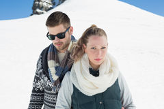 在温暖的衣物的夫妇在下雪的小山前面 图库摄影