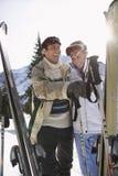 在温暖的衣物的快乐的滑雪夫妇有滑雪的 库存图片
