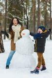 在温暖的衣物的愉快的家庭 使雪人的微笑的母亲和儿子室外 冬天活动的概念 免版税库存图片