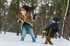 在温暖的衣物的愉快的家庭 室外微笑的母亲和儿子戏剧的雪球 冬天活动的概念 图库摄影